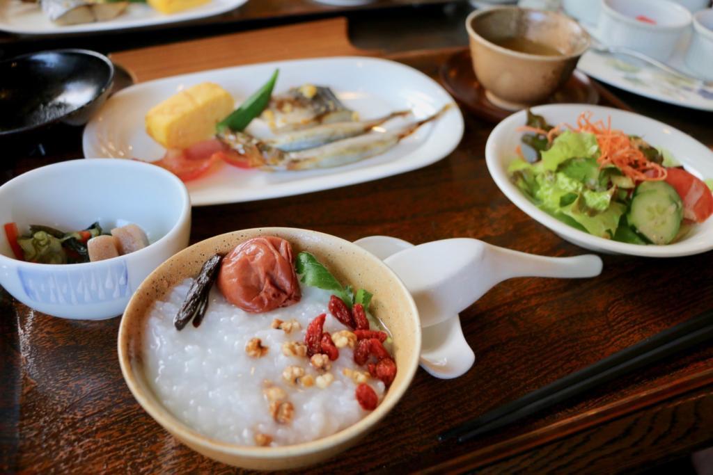 お茶碗にたっぷりのお粥、焼き魚、卵焼き、ベーコン、サラダ