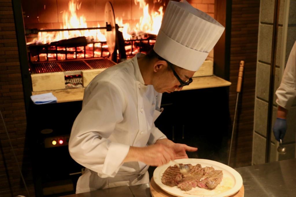 薪火で焼いたお肉を手早くカット