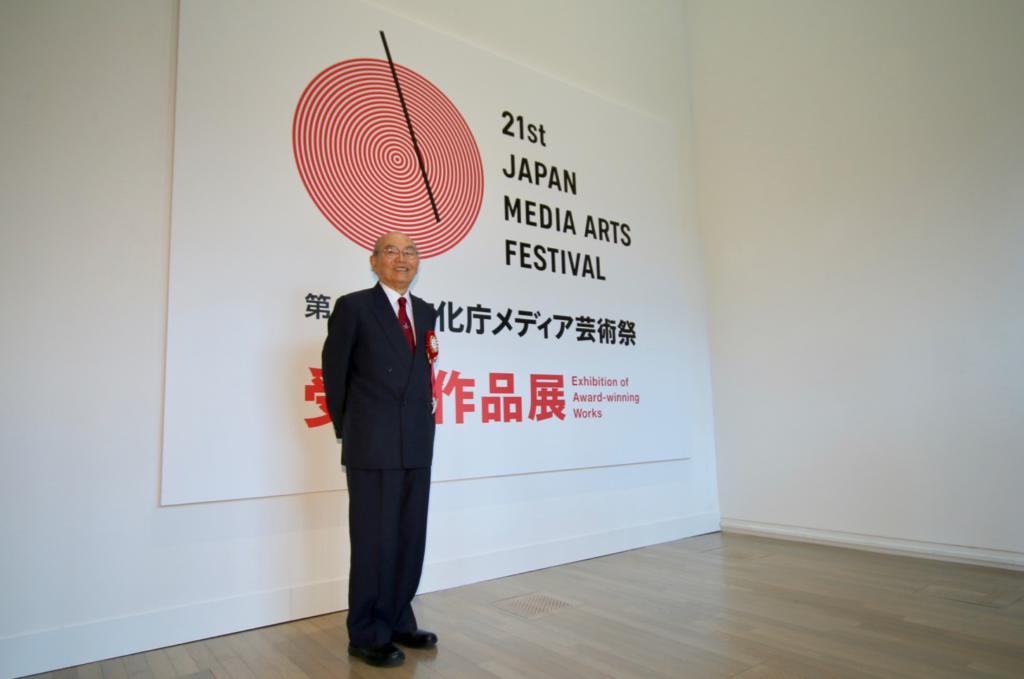 作品展のエントランスで記念撮影に応じる田宮俊作会長